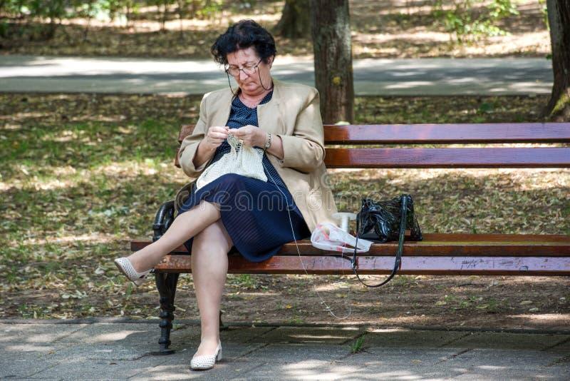 Senhora superior que senta-se no banco no parque e na toalha de mesa de confecção de malhas imagens de stock