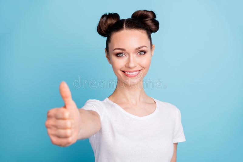 Senhora surpreendente que guarda o polegar acima de recomendar a boa qualidade do fundo azul do t-shirt ocasional branco do desga foto de stock royalty free