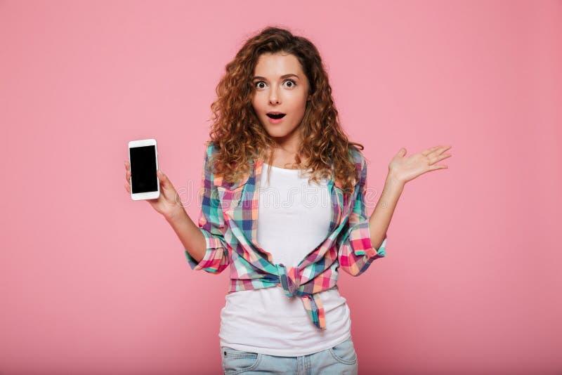 Senhora surpreendida que mostra o smartphone com a tela vazia isolada fotos de stock
