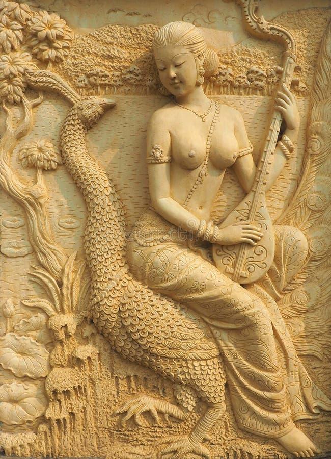 A senhora tailandesa jogou a música que senta-se no pavão traseiro imagens de stock royalty free