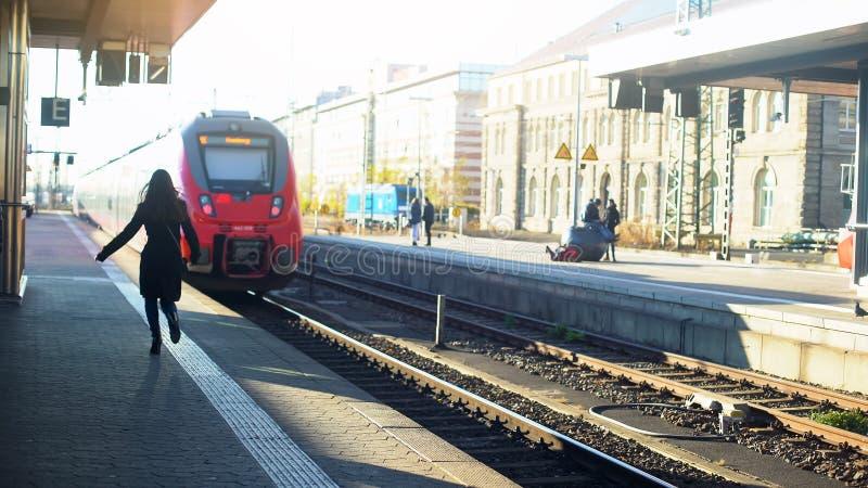 Senhora tarde para o trem, correndo na plataforma, vida na cidade moderna, tempo-gestão foto de stock