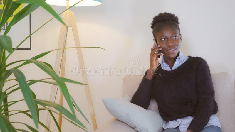 A senhora tem a conversa telefônica no apartamento fotografia de stock