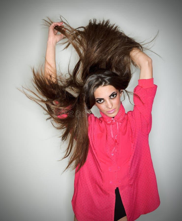 Senhora triguenha nova que joga com cabelos longos imagens de stock royalty free