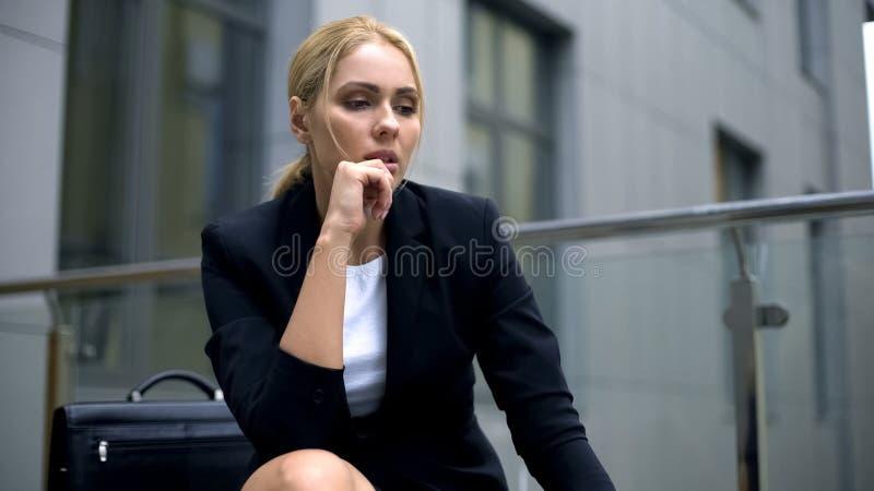 Senhora triste do negócio que pensa sobre o trabalho duro e as dificuldades, falta da experiência fotografia de stock