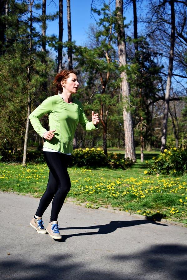 Senhora vermelha nova do cabelo na camisa verde que faz seu treinamento corrido no parque 1 fotos de stock royalty free
