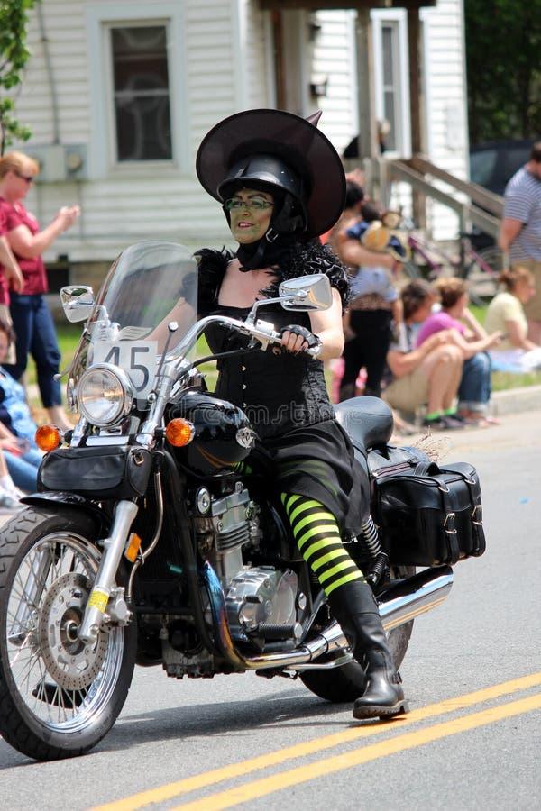 Senhora vestida como a motocicleta da equitação da bruxa através da cidade em toda a parada da onça das coisas, Chittenango, New  fotografia de stock royalty free