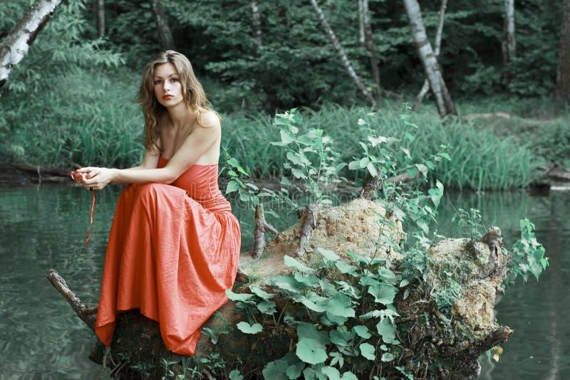 Senhora vestida vermelha no banco verde imagens de stock