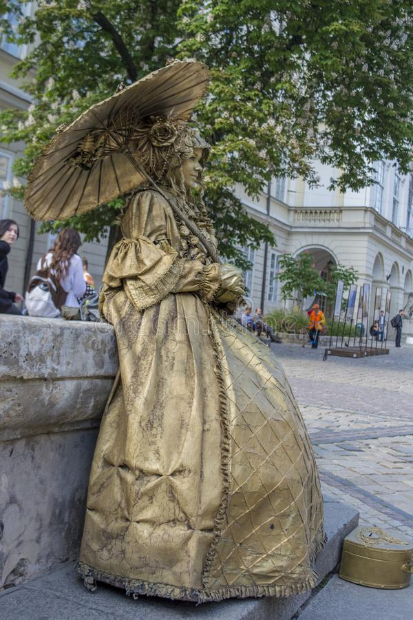 A senhora vestiu-se acima como a estátua de bronze na rua imagens de stock