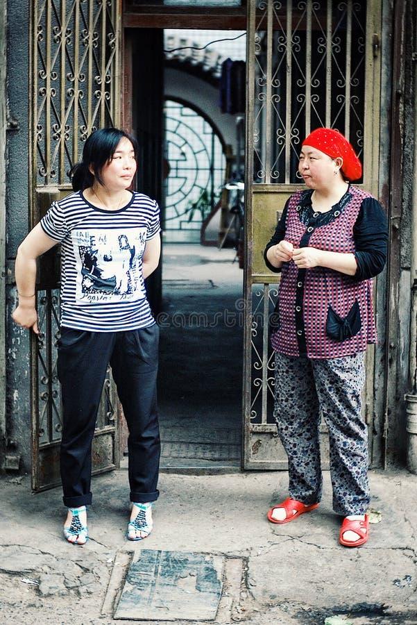 Senhoras chinesas que falam fora de sua casa imagem de stock