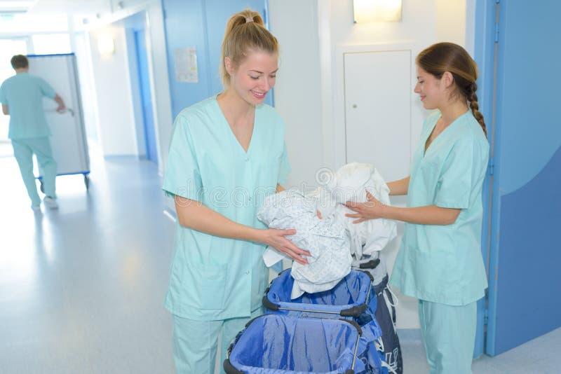 Senhoras de limpeza que fazem tarefas domésticas na clínica imagens de stock royalty free