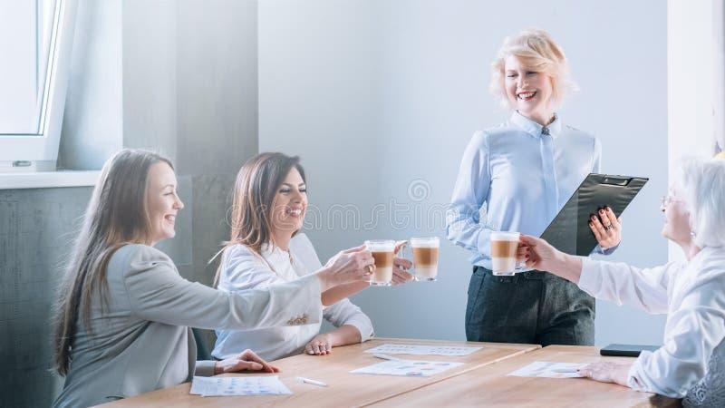 Senhoras do neg?cio dos elogios que comemoram o latte do tinido imagens de stock