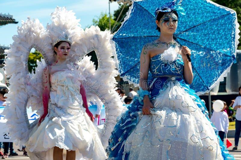Senhoras do vestido de fantasia com o azul extremo do dia da composição com guarda-chuvas imagens de stock royalty free