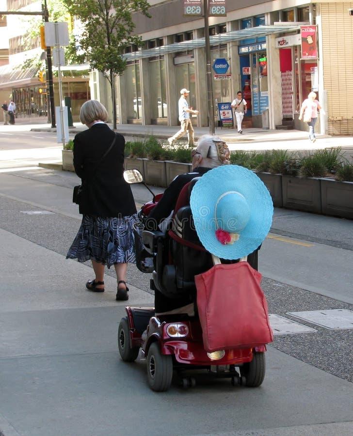 Senhoras idosas que andam e que montam um 'trotinette' da mobilidade na baixa de Vancôver imagens de stock royalty free