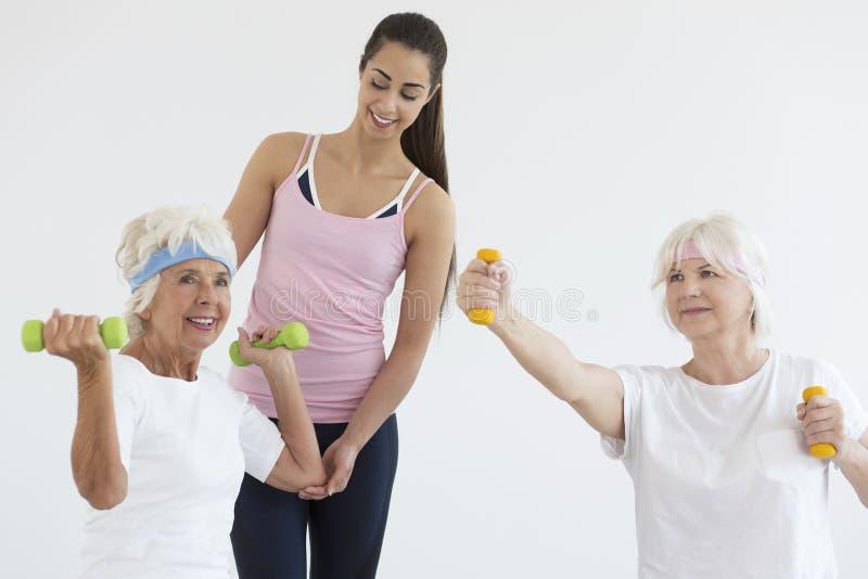 Senhoras mais idosas durante a formação dos braços imagens de stock royalty free