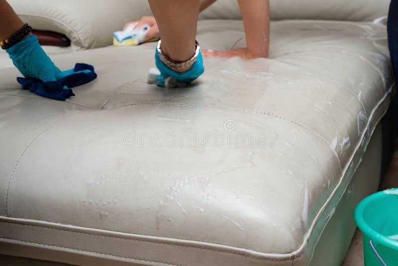 Senhoras que limpam o sof? de couro imagens de stock royalty free