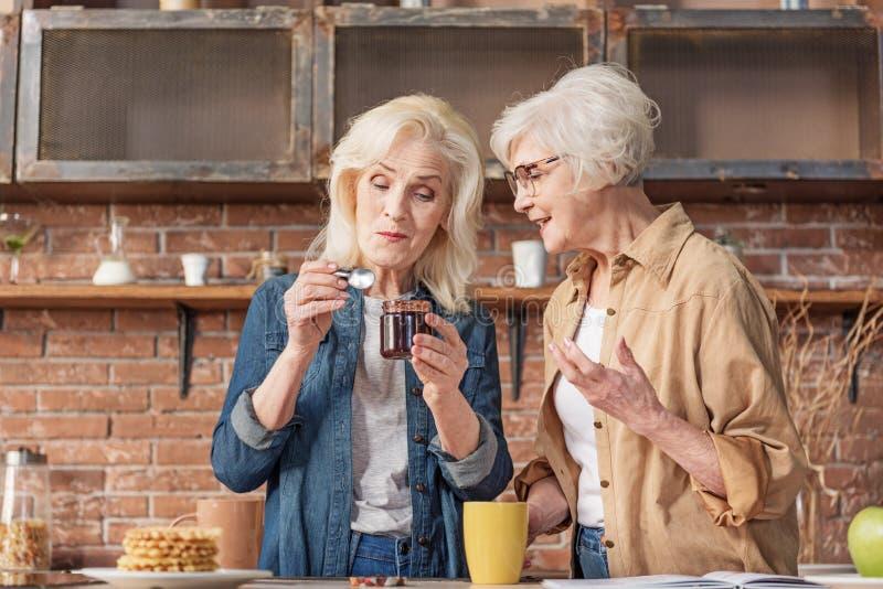 Senhoras superiores alegres que compartilham da experiência sobre a preparação dos alimentos imagem de stock royalty free