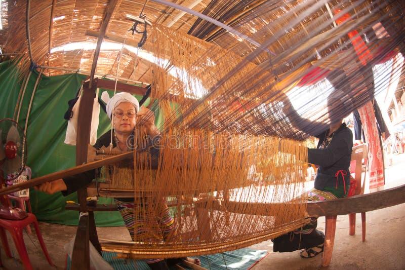 Senier visar asiatiska minoritetkvinnor till tillvägagångssättet av att göra thailändskt siden- väva i litet väva maler royaltyfri bild
