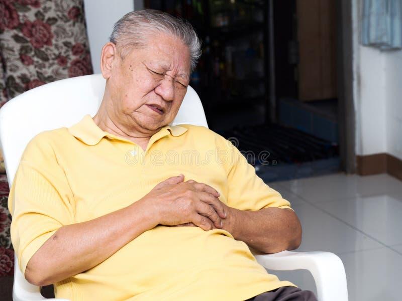 Senile asiatische Männer, die auf einem Stuhl am Wohnzimmer mit Herzinfarkten sitzen Beide alter Mann ` s Hände auf Brust wegen s stockfotografie