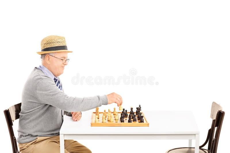 Seniler alter Mann, der ein Spiel des Schachs allein spielt lizenzfreie stockbilder