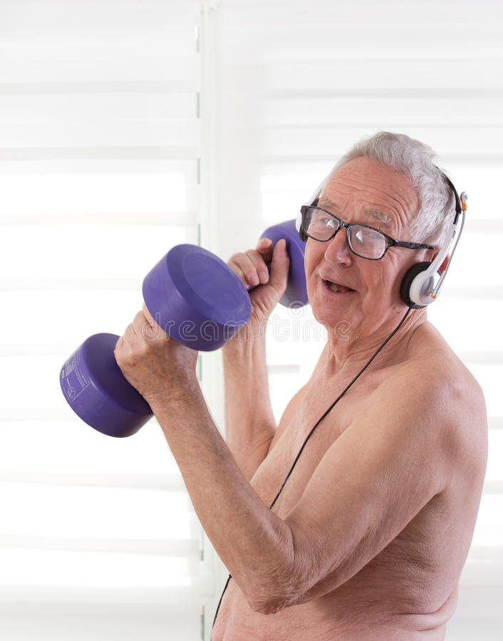 Senioe man with dumbbells and headset stock photo