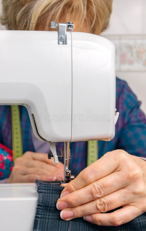 Senion seamstress woman working on sewing machine. Senior seamstress woman working with clothing item on a sewing machine stock photos