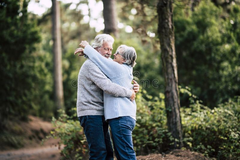 Senior active couple enjoying the outdoor nature forest with hugs and love together - forever life concept with mature man and royalty free stock photography