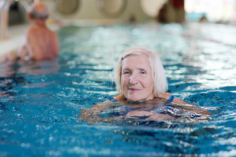Senior active lady swims in the pool. Happy healthy senior woman enjoying active lifestyle swimming in the pool royalty free stock photo