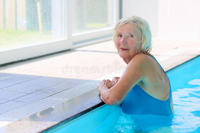 Senior active lady swims in the pool. Happy healthy senior woman enjoying active lifestyle swimming in the pool stock images
