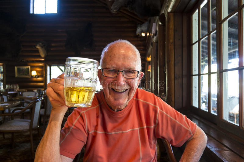 Senior active man drinking beer stock images