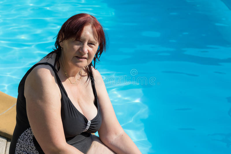 Senior active woman by a swimming pool stock photo
