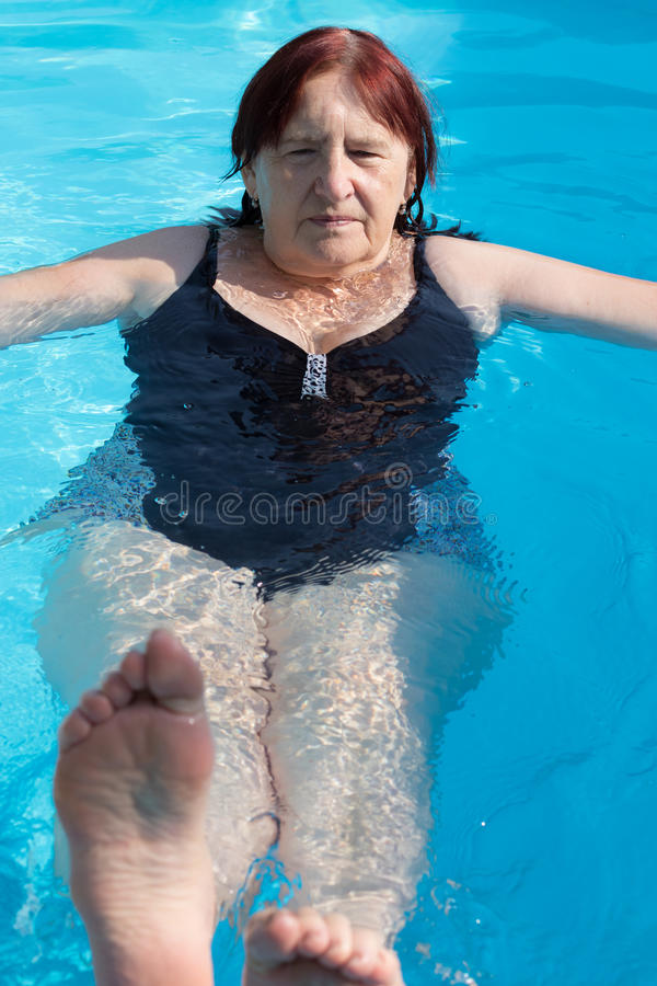 Senior active woman swimming stock photography