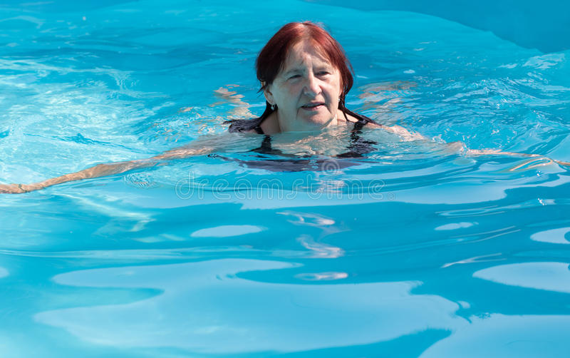 Senior active woman swimming stock image