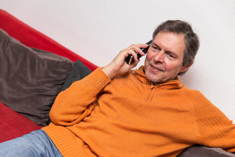 Senior adult on a couch with phone. Is phoning royalty free stock photography