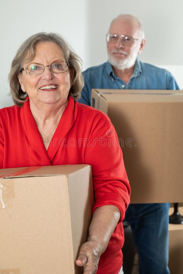 Senior Adult Couple Carrying Moving Boxes stock photo