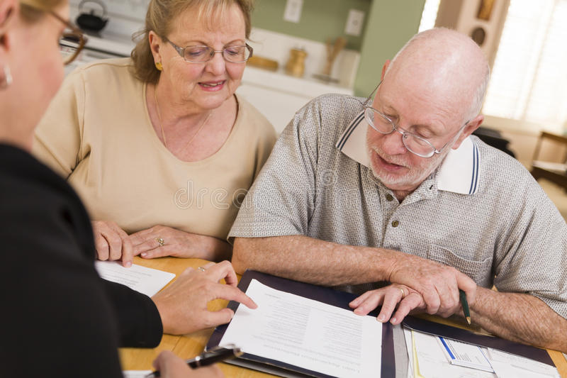 Senior Adult Couple Going Over Papers in Their Home with Agent.  royalty free stock photography