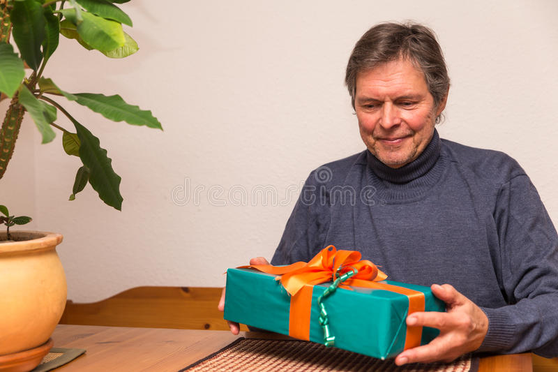Senior adult gets a gift. Senior citizen gets a green gift stock photo