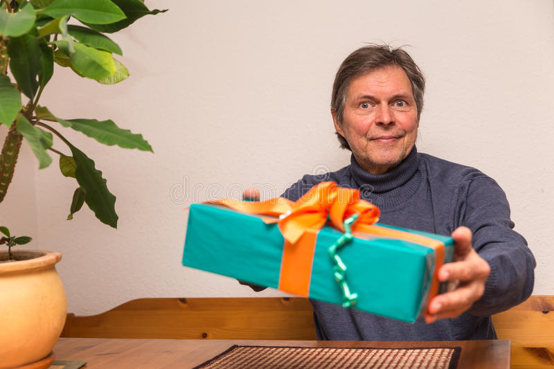 Senior adult gets a present. Senior adult gets a green present royalty free stock images