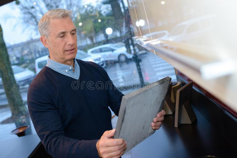 Senior adult holding frame in shop stock image