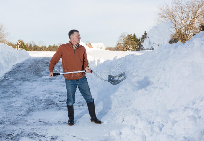 Senior adult man finishes digging out drive in snow. Senior man with snow shovel finishes removing snow drifts on driveway by digging out from the blizzard stock images