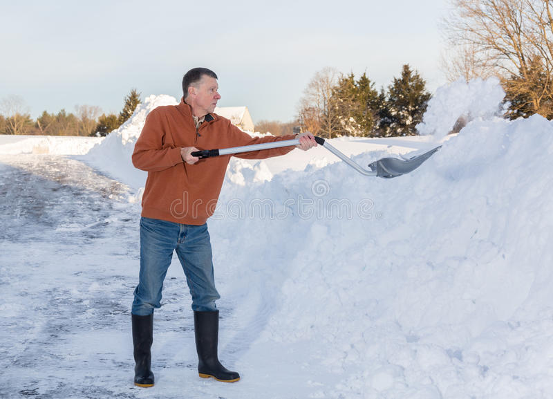 Senior adult man finishes digging out drive in snow. Senior man with snow shovel finishes removing snow drifts on driveway by digging out from the blizzard stock photos
