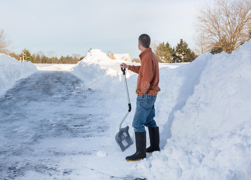 Senior adult man happy after digging out drive in snow. Senior man with snow shovel looking content after removing snow drifts on driveway by digging out from royalty free stock image