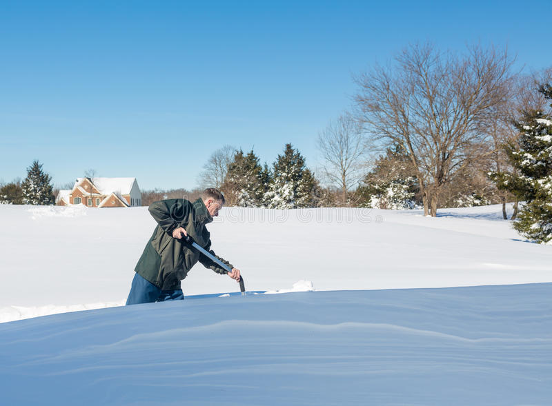 Senior adult man trying to dig out drive in snow. Senior man with snow shovel looking at snow drifts on driveway as he tries to dig out from the blizzard stock images