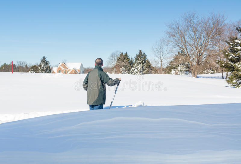 Senior adult man trying to dig out drive in snow. Senior man with snow shovel looking at snow drifts on driveway as he tries to dig out from the blizzard stock image