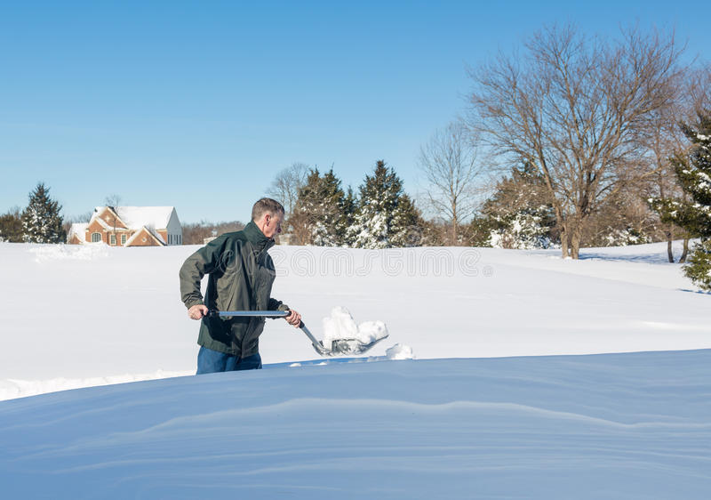 Senior adult man trying to dig out drive in snow. Senior man with snow shovel looking at snow drifts on driveway as he tries to dig out from the blizzard royalty free stock photography