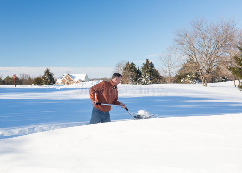Senior adult man trying to dig out drive in snow. Senior man with snow shovel looking at snow drifts on driveway as he tries to dig out from the blizzard royalty free stock photos