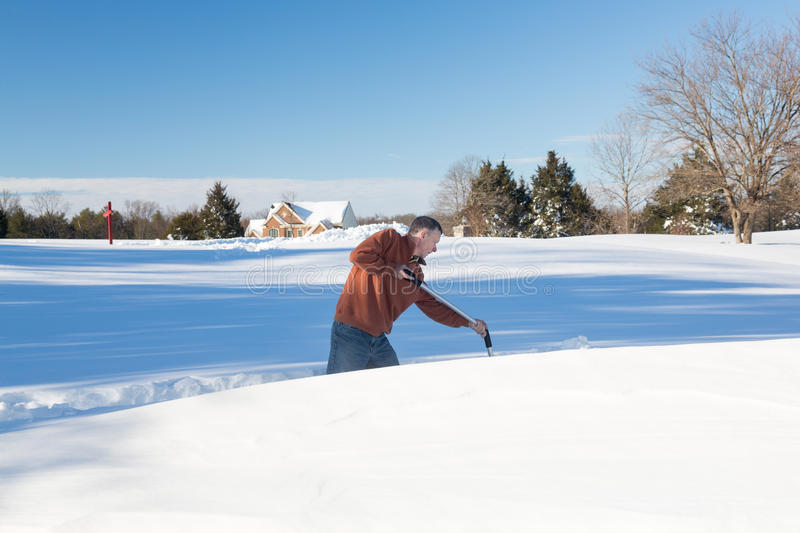 Senior adult man trying to dig out drive in snow. Senior man with snow shovel looking at snow drifts on driveway as he tries to dig out from the blizzard royalty free stock photo