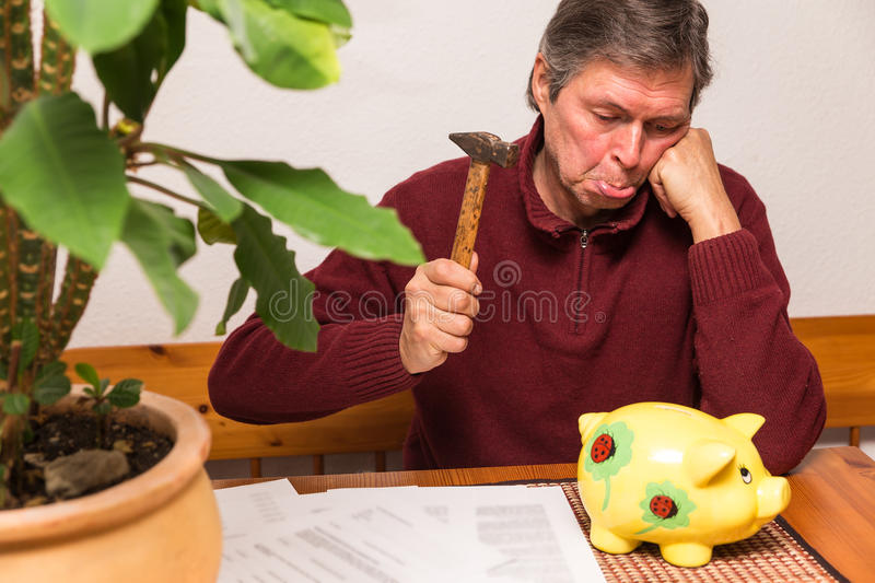 Senior adult with piggy bank. Senior adult try to smash piggy bank stock image