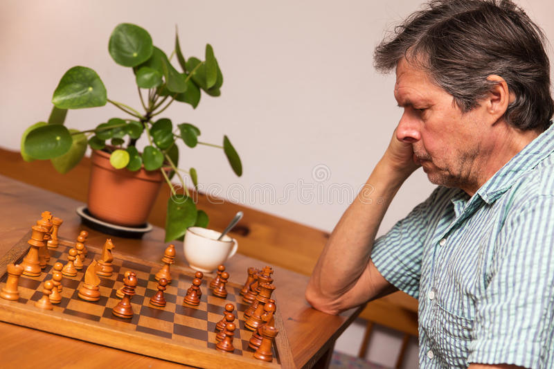 Senior adult is playing chess stock photos