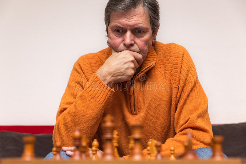 Senior adult is playing chess. Portrait of an senior adult, playing chess stock image