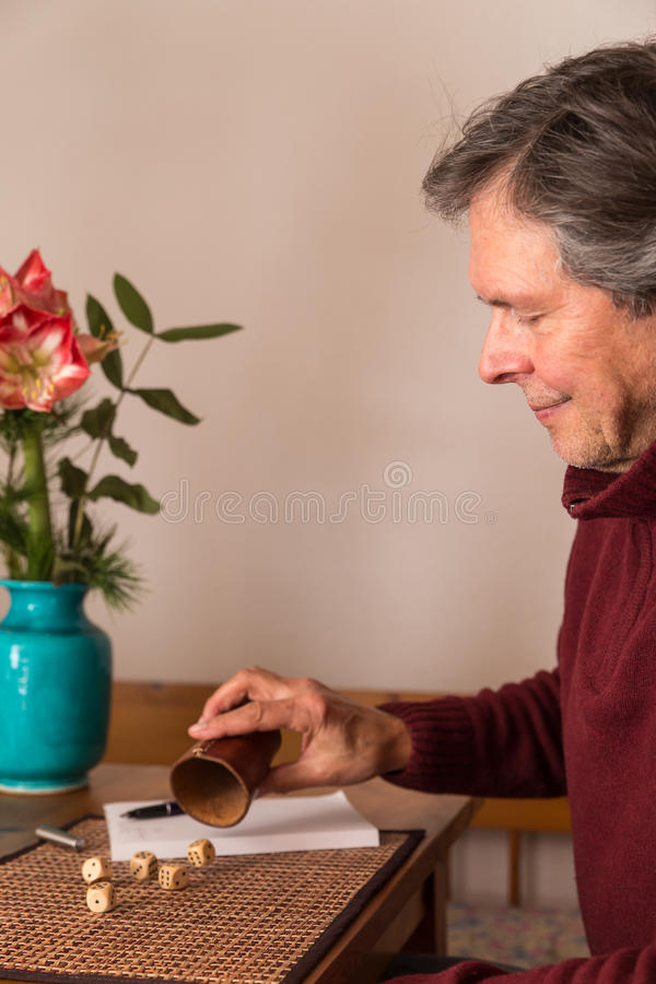 Senior adult plays with dices. Senior adult gambles with dices stock photography